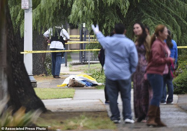 Evacuated office workers stand by, with a deceased shooting victim down on the sidewalk Tuesday